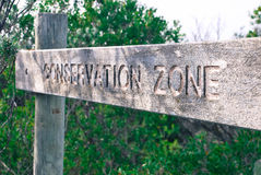 Conservation Zone Wooden Sign. In between the brush / bush. Carved letters on the wood. Sign nailed to the wooden poles Royalty Free Stock Images