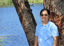 Conservative Asian. A middle age Asian female or Filipina dressed conservatively posed by a tree by a pond royalty free stock photo