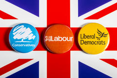 Conservatives, Labour and Liberal Democrats. LONDON, UK - MAY 2ND 2017: Conservatives, Labour and Liberal Democrat pin badges over the UK flag, symbolizing the Royalty Free Stock Images
