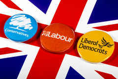 Conservatives, Labour and Liberal Democrats. LONDON, UK - MAY 2ND 2017: Conservatives, Labour and Liberal Democrat pin badges over the UK flag, symbolizing the Stock Photo