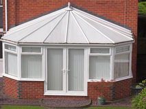 Conservatory. White brick and upvc conservatory at rear of house stock photo