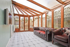 Conservatory. Extension of a family home with leather sofa and tiled floor Stock Photo