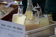 Conserve en vinagre el jugo y el jugo de la chucrut en el mercado del granjero imagen de archivo