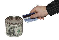 Conserve of money. A man opens a canned money by credit card Royalty Free Stock Photography
