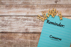 Conserve Reminder motivational concept. On note paper and wooden board Stock Image