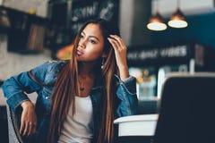 Conservi la giovane donna splendida di previsione di download in blue jeans che raffreddano in un club Fotografie Stock