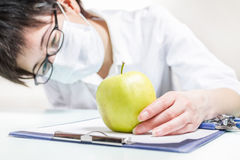 Consider apple. Doctor examines big green apple Royalty Free Stock Photos