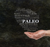 Consider The Paleo Diet. Chunky male hand with cupped palm  and a PALEO word cloud floating above on a dark stone cave wall effect background with copy space Stock Photo