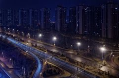 Considerando il grattacielo in una fila ed in un'autostrada di notte Immagine Stock