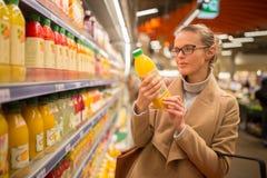 Consideravelmente, compra da jovem mulher para seu suco de fruto favorito imagem de stock royalty free