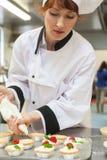 Consideravelmente concentrando o cozinheiro chefe principal que prepara a sobremesa Imagens de Stock Royalty Free