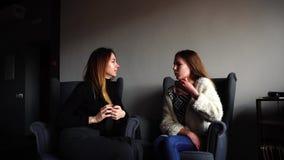 Consideravelmente duas meninas discutem segredos da beleza e sentam-se em poltronas cinzentas no café à moda no dia de inverno n video estoque