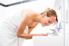 Consideravelmente fêmea escovando seus dentes na frente do espelho imagem de stock royalty free
