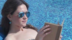 Consideravelmente fêmea no livro de leitura na praia, lazer dos óculos de sol video estoque