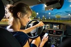 consideravelmente, jovem mulher que conduz seu carro moderno na noite, em uma cidade fotos de stock