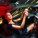 consideravelmente, jovem mulher que conduz seu carro moderno na noite, em uma cidade Fotografia de Stock Royalty Free