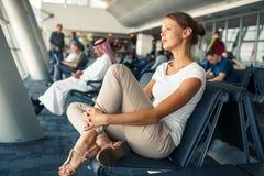 Consideravelmente, jovem mulher que espera em uma área da porta de um aeroporto moderno fotos de stock