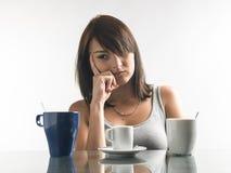 Consideravelmente, jovem mulher que olha canecas de café no fundo brilhante Fotografia de Stock Royalty Free