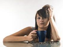 Consideravelmente, jovem mulher que olha canecas de café no fundo brilhante Imagem de Stock Royalty Free