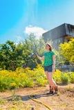Consideravelmente jovem mulher que tem o divertimento no jardim do verão com a mangueira de jardim que espirra a chuva Conceito d imagens de stock