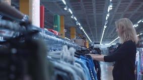 Consideravelmente louro está escolhendo a roupa na loja video estoque