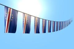 Consideravelmente muitas bandeiras ou bandeiras de Cabo Verde que penduram a diagonal na corda no fundo do céu azul com foco maci ilustração stock