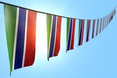 Consideravelmente muitas bandeiras ou bandeiras de Gâmbia que penduram a diagonal na corda no fundo do céu azul com foco macio -  ilustração stock