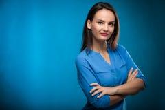 Consideravelmente, mulher de negócios nova contra o fundo azul fotografia de stock