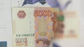 Considere un billete de banco de cinco mil rublos, un aumento con una lupa almacen de metraje de vídeo