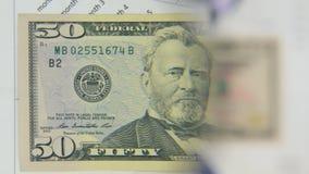 Considere un billete de banco de cincuenta dólares, un aumento con una lupa almacen de video