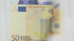 Considere un billete de banco de cincuenta euros, un aumento con una lupa almacen de video