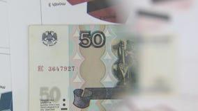 Considere un billete de banco de cincuenta rublos, un aumento con una lupa almacen de video