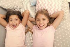 Consideri il pigiama party di tema Tradizione senza tempo di infanzia del pigiama party Ragazze che si rilassano sul letto Concet immagine stock
