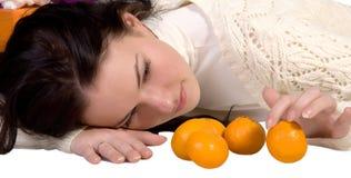 She considers the orange tangerines Stock Photography