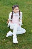 Consiga feliz Las trenzas peinado y auriculares modernos de la muchacha gozan para relajarse Secretos a criar al niño feliz Mucha imagenes de archivo