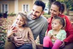 Consiga la sonrisa para hacer la cámara, muchacha toman una imagen de toda la familia foto de archivo libre de regalías
