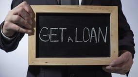 Consiga un préstamo escrito en la pizarra, hombre de negocios que lleva a cabo la muestra, concepto del negocio metrajes
