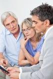 Consigliere finanziario che comunica con anziano fotografia stock