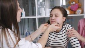 Consiglio nell'ambulatorio Una madre e una figlia un adolescente sull'esame medico Un medico esamina una ferita stock footage