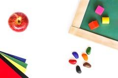 Consiglio scolastico, blocchi colorati, mela rossa, pastelli di cera, carta colorata che si trova su un fondo di legno bianco Immagini Stock