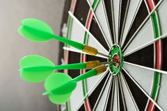 Consistency. Three green darts pinned on the center of dartboard royalty free stock image