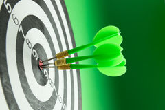 Consistency. Three green darts pinned right on the center of dartboard royalty free stock images