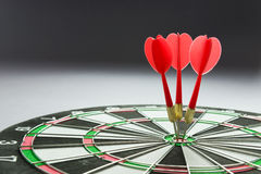Consistency. Three red darts pinned right on the center of dartboard royalty free stock images