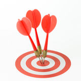 Consistency. Three red darts pinned right on the center of target stock photography