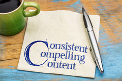 Consistent, compelling content on napkin. Consistent, compelling content - advice for bloging and social media marketing - handwriting on a napkin with cup of royalty free stock photography