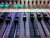 Consola audio profesional del mezclador con los botones negros para igualar sonidos foto de archivo