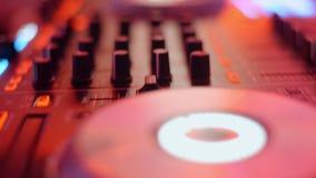 Consola de DJ, mezclador de la música en el partido de disco en el escritorio del regulador del club nocturno, luces multicoloras metrajes