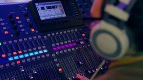 Consola de mezcla en la iluminación del color en la cual trabajo de las manos de las mujeres metrajes