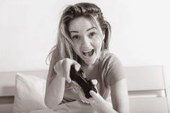 Consola que juega adolescente de la muchacha que se sienta para arriba en cama Fotos de archivo libres de regalías