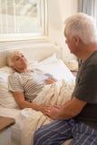 Consolazione dell'uomo senior della sua moglie malata a letto immagini stock libere da diritti